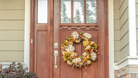 Panorama frame Front door with dried flower wreath day. Wooden front door with dried flower to a residential property wreath hanging below the glass panel on a covered porch 스톡 콘텐츠