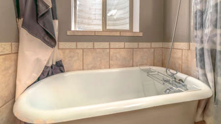 Panorama frame Close up of a bathtub in side a bathroom with shower curtains and window 스톡 콘텐츠