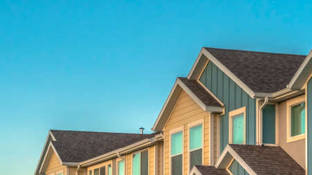 Panorama frame Exterior of upper storey of townhomes with blue sky background on a sunny day. The townhouses have pitched roofs, square windows, and blue and cream wall.