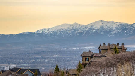 Panorama frame Hill homes with distant snow capped mountain toweing over lake and valley. Picturesque landscape and scenery under cloudy sky at sunset.