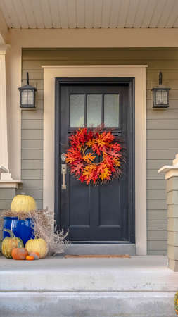 Vertical Colorful autumn wreath hanging on a front door. Colorful autumn wreath hanging on a blue front door of a house with covered front porch with steps and railing