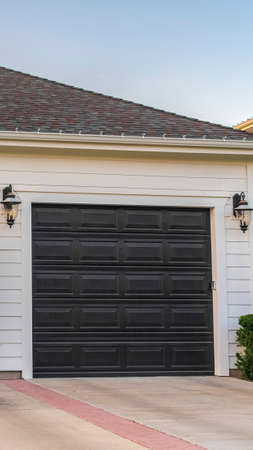 Vertical Double garage unit attached to a suburban house. Double garage unit attached to a suburban house in a close up street view with closed doors 스톡 콘텐츠
