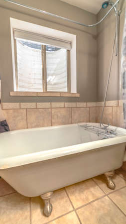 Vertical frame Close up of bathtub and shower inside a bathroom with tiles on wall and floor