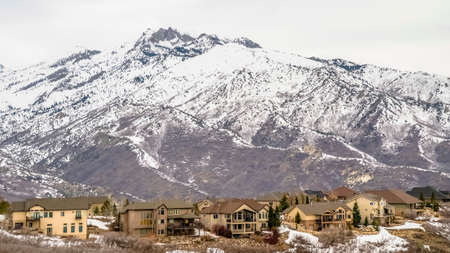 Panorama frame Winter landscape with homes on a hill overlooking a striking snowy mountain 스톡 콘텐츠