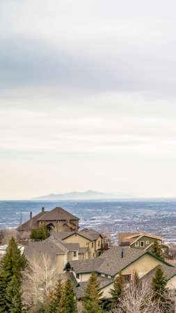 Vertical Aerial view of houses in the valley with mountain and horizon in the distance 스톡 콘텐츠