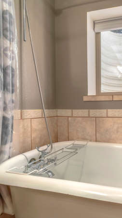 Vertical Close up of a bathtub in side a bathroom with shower curtains and window 스톡 콘텐츠