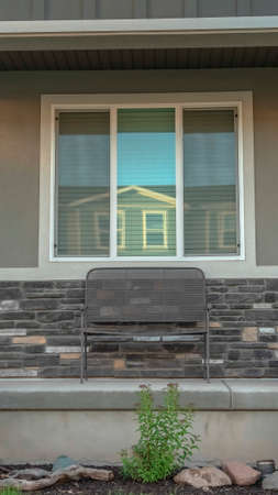 Vertical frame Front porch and yard of a family home with concrete outdoor stairs and gray door. A bench is placed against the window and stone brick wall.