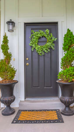 Vertical Gray front door of a home with green wreath and flanked by tall potted plants