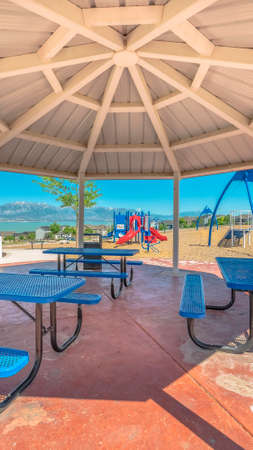 Vertical frame Octagon pavilion with blue picnic tables and view of lake and Mount Timpanogos