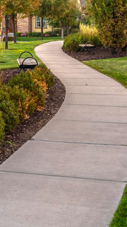 Vertical frame Paved walkway through a landscaped garden day. Paved walkway through a landscaped garden or park with shrubs and neat green lawns leading to a distant building behind trees Reklamní fotografie