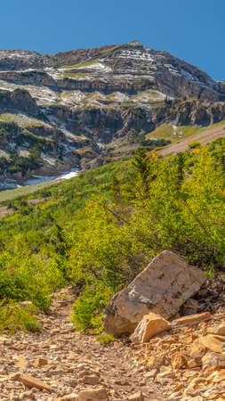 Vertical frame View from a hiking trail on Mount Timpanogos. Scenic vertical view from a hiking trail on Mount Timpanogos, Utah, USA of a rugged mountain with remnants of snow and valley with river