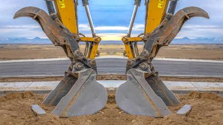 Tractor symmetry with open scooper on an excavator facing away Stock fotó