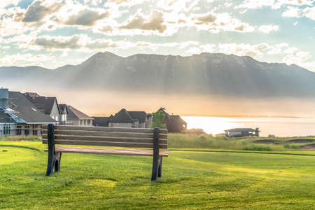 Golf course bench with scenic view of homes lake and mountain on a sunny day Stock Photo