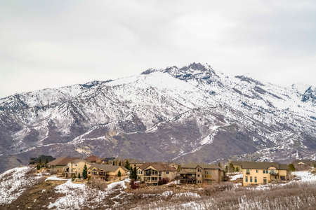 Winter landscape with homes on a hill overlooking a striking snowy mountain