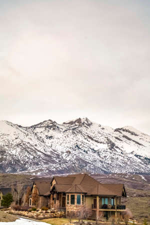 Beautiful house with balcony and view of a snowy mountain against cloudy sky