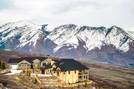 Luxury homes on a hill with striking view of snow capped mountain against sky