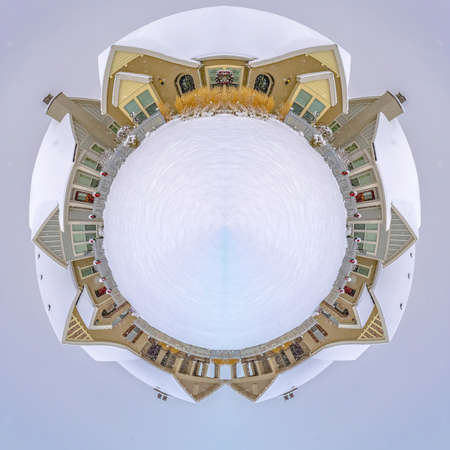 Circular design made from a winter village with fresh snow covering everything and white center