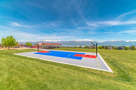 Outdoor basketball court at a park with view of snow capped mountain and lake