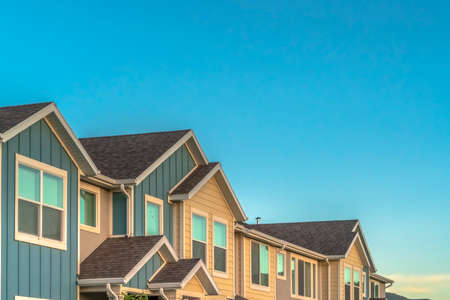 Exterior of upper storey of townhomes with blue sky background on a sunny day 스톡 콘텐츠