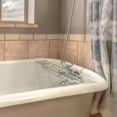 Square frame Close up of a bathtub in side a bathroom with shower curtains and window