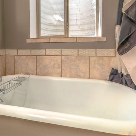 Square Close up of a bathtub in side a bathroom with shower curtains and window