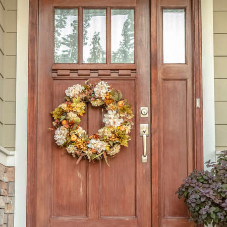 Square frame Front door with dried flower wreath day 스톡 콘텐츠
