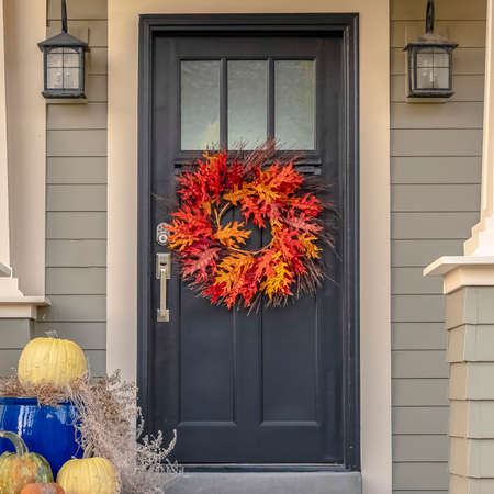 Square Colorful autumn wreath hanging on a front door 스톡 콘텐츠