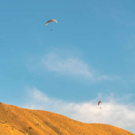 Square Paragliders flying over a huge mountain viewed on a beautiful sunny day