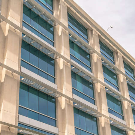 Square frame Modern building facade close up with glass windows and sunlit concrete wall