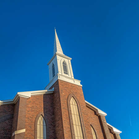 Square frame Church with classic red brick exterior wall and white steeple against blue sky Stock fotó