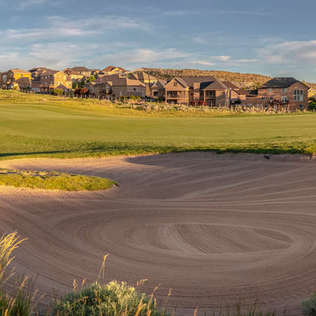 Square frame Panorama of a large sand trap on a golf course. Panoramic view of a large sand trap on the fairway of a golf course. A view to a town in the background on a sunny day