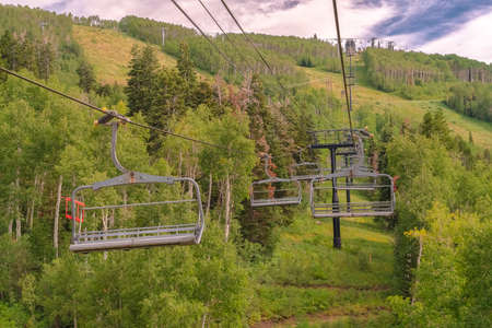 Vibrant green summer landscape of trees and mountain beneath chairlifts Zdjęcie Seryjne