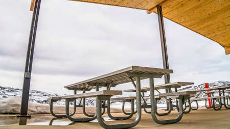 Panorama frame Pavilion with tables and benches under the wooden ceiling at a park in winter