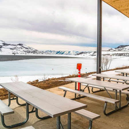 Square Picnic pavilion overlooking a snowy winter landscape of lake and mountain