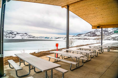 Picnic pavilion overlooking a snowy winter landscape of lake and mountain