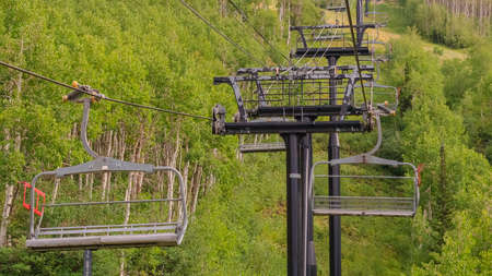 Panorama frame Chairlifts on cables over ski mountain with thick green trees during off season