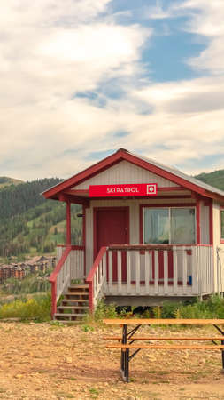 Vertical Off season in Park City with Ski Patrol cabin against mountain and cloudy sky