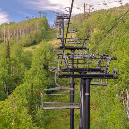 Square frame Chairlifts on cables over ski mountain with thick green trees during off season