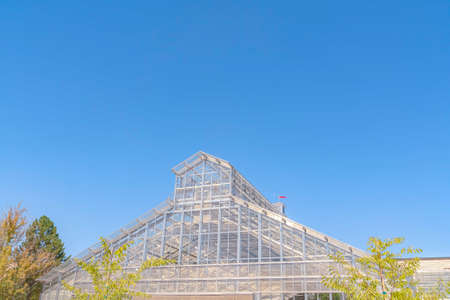 Exterior of a greenhouse with roof made of glass panels against blue sky