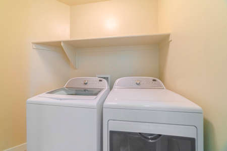 Washing machine and dryer inside a laundry room with shelf and beige wall Zdjęcie Seryjne