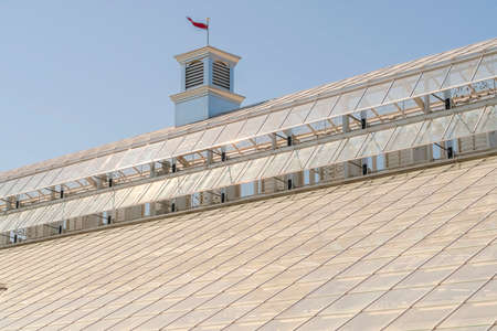 Close up of roof of a greenhouse with glass panels against sky on a sunny day Zdjęcie Seryjne
