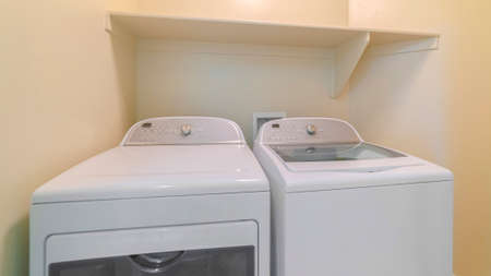 Panorama frame Washing machine and dryer inside a laundry room with shelf and beige wall