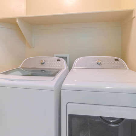 Square Washing machine and dryer inside a laundry room with shelf and beige wall Zdjęcie Seryjne