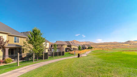 Panorama frame Houses and pathway along a golf course with scenic mountain and blue sky view