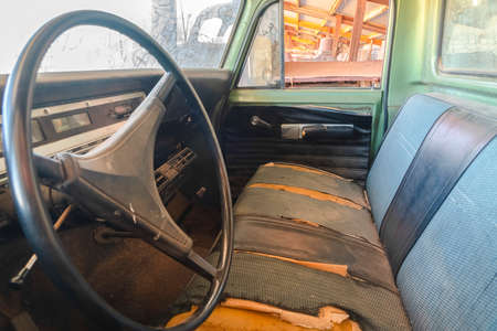Old vintage car with close up of the steering wheel and dirty interior. The rusty car has peeling green paint and damaged front seats.