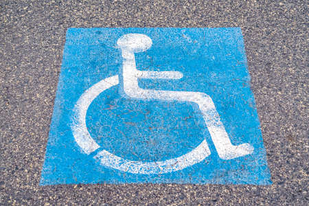 Disabled or Handicapped road sign painted on asphalt in a restricted area for wheelchair access
