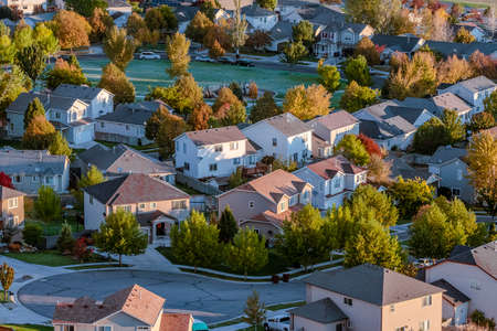 Modern urban housing estate with small park and trees in autumn in an aerial rooftop view Stock fotó