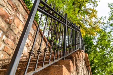 Close up of metal railing and stone treads of a staircase against stone fence. Outdoor stairway with lush green trees and bright sky in the background.