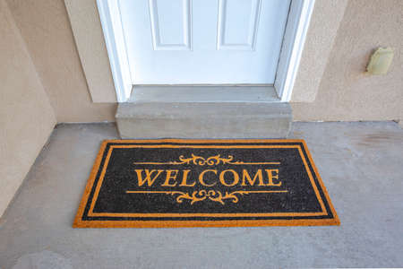 Black and brown Welcome doormat by the doorstep of home with white front door. Close up view of the entryway of a house with concrete floor and wall.
