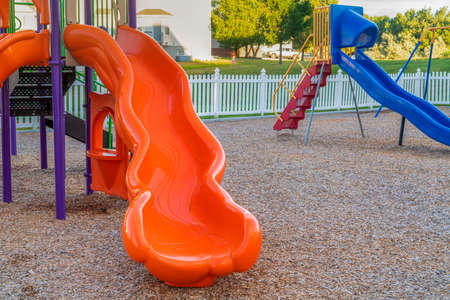 Close up of bright and shiny orange slide at a park with childrens playground. Focus on a playground equipment with white fence, blue skide, and homes in the background. Foto de archivo